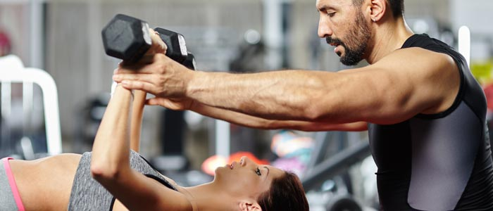 woman and trainer at the gym lifting dumbbells