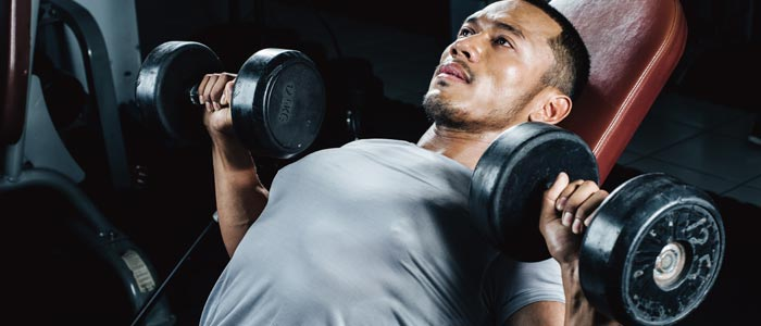 man on a weight bench lifting dumbbells