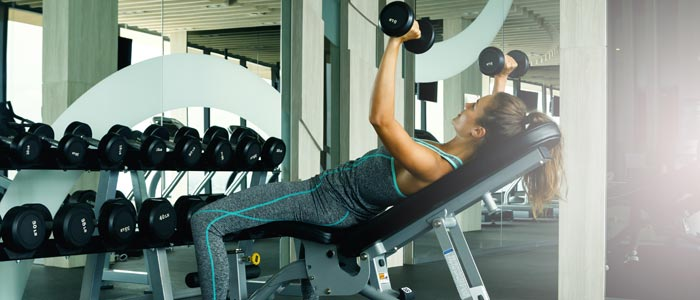 woman performing bench press with dumbbells
