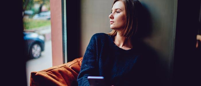 woman sat in a window looking outside