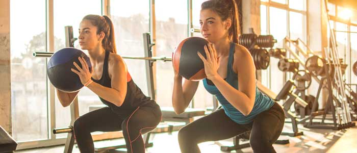 Women using exercise balls in a gym