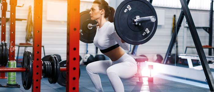 Woman squatting in a power rack