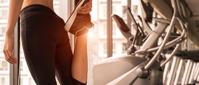 woman stretching before and after running on treadmill