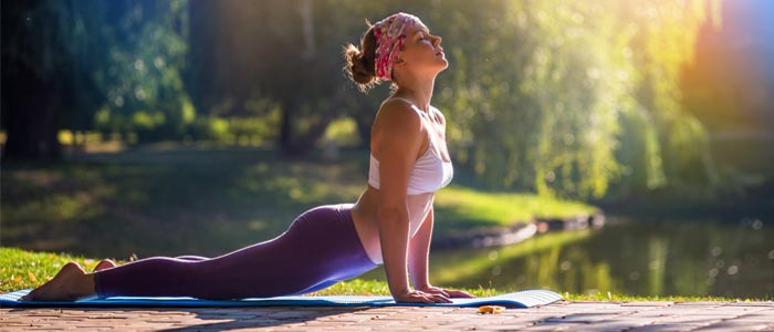 woman doing the cobra pose by a lake