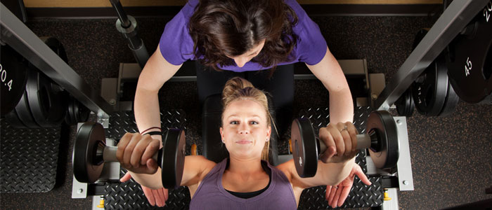 Woman being a gym spotter