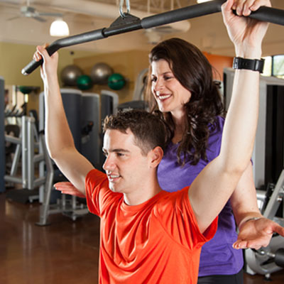 Woman helping man in a gym