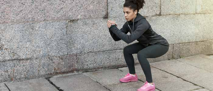 Woman squatting for compound exercise