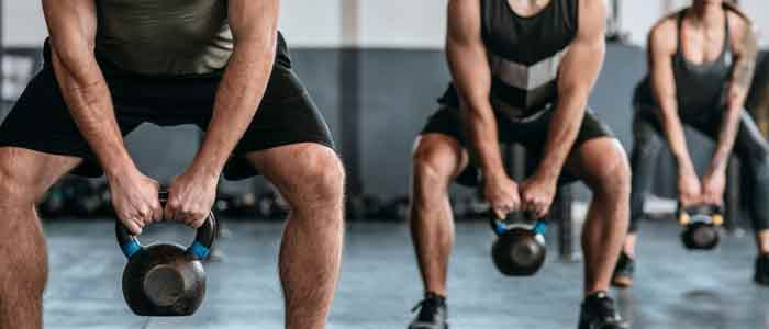 people lifting kettlebells in a gym