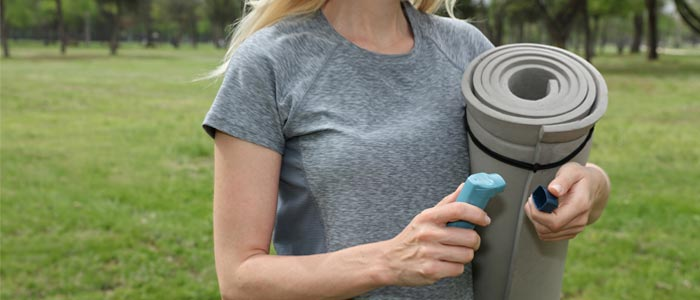 Woman about to exercise with asthma inhaler