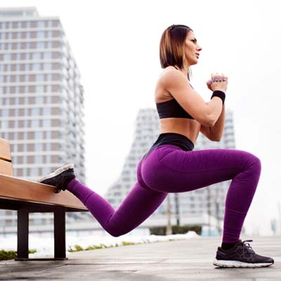 Woman doing split squats on a bench