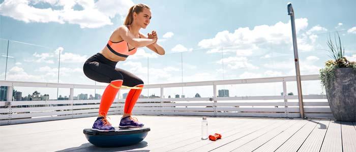 Woman using a bosu ball to squat