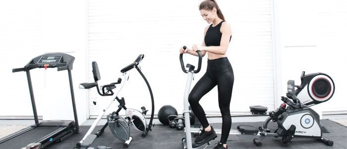 Woman using cardio machines in her garage gym
