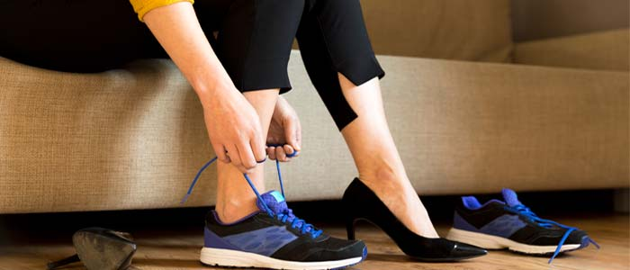 Close up of business woman changing into workout shoes