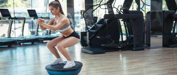 Woman performing a squat on a Bosu® ball