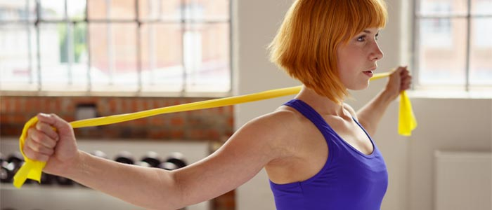 Woman using a resistance band behind her head