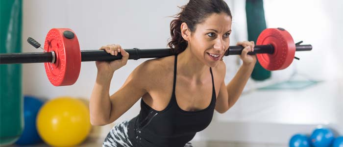 Woman weight training with a barbell