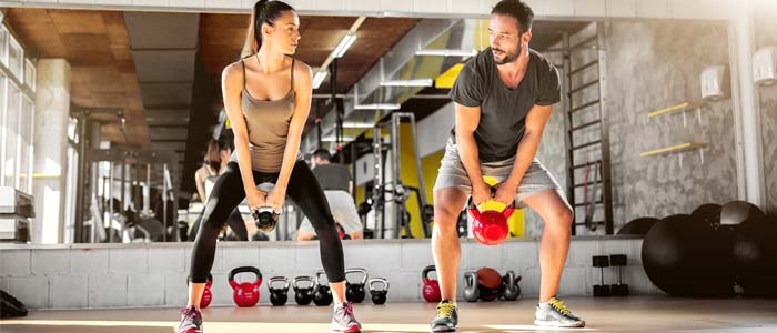 Couple doing kettlebell swings