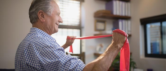Elderly man using resistance bands at home