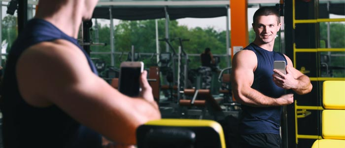 person taking selfie in the gym mirror