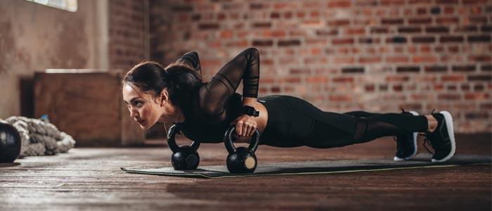Woman doing kettlebell push ups