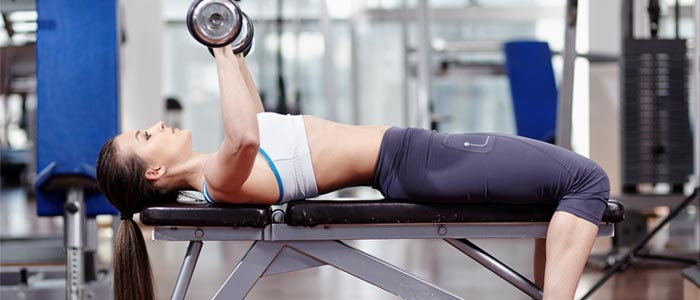 Person bench pressing dumbbells