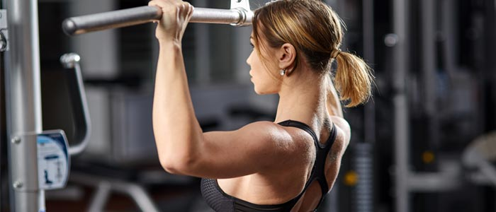 Person doing lat pull downs for lean muscle