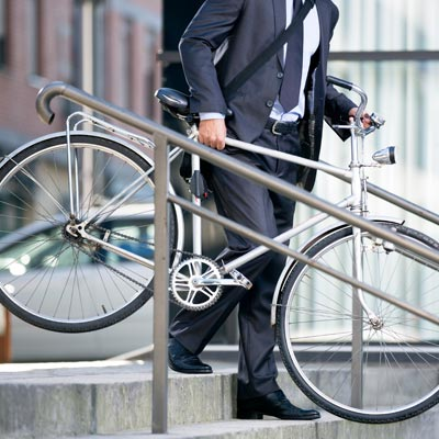 Person carrying their bike to work