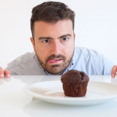 Person tempted by bad cupcake habit