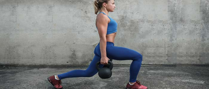 Perosn doing lunges with kettlebell