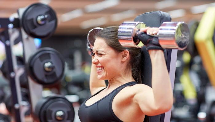 person doing dumbbell shoulder presses