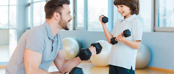 man and boy using dumbbells