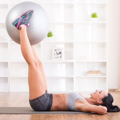 person using an exercise ball for leg raises