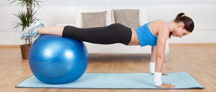 person doing a decline push up using an exercise ball