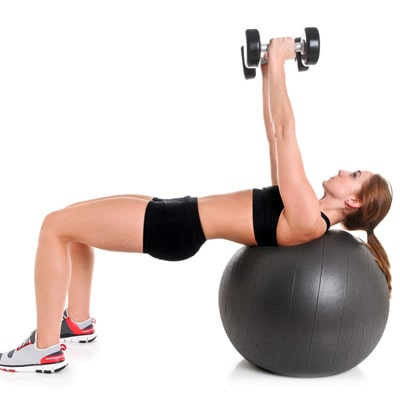 a person using dumbbells and an exercise ball to chest press