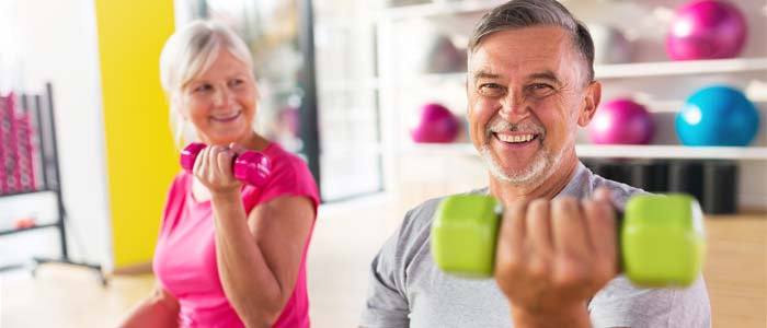 A man and woman exercising together with dumbbells
