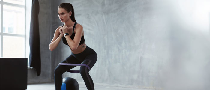 Woman doing squats with a resistance band