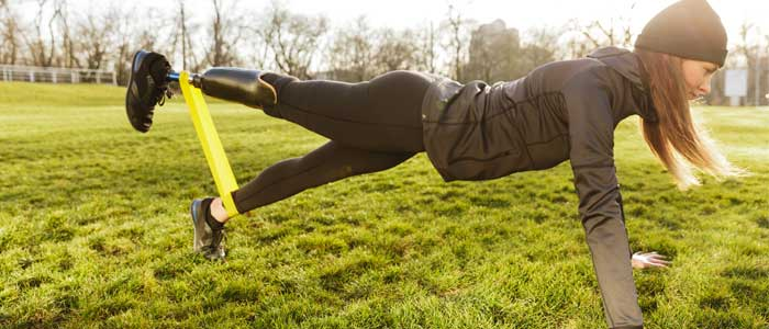 woman doing push ups outdoors with resistance bands