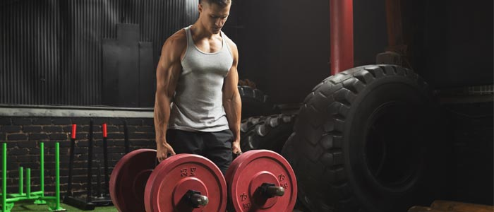 Man holding farmers walk equipment preparing to perform the exercise