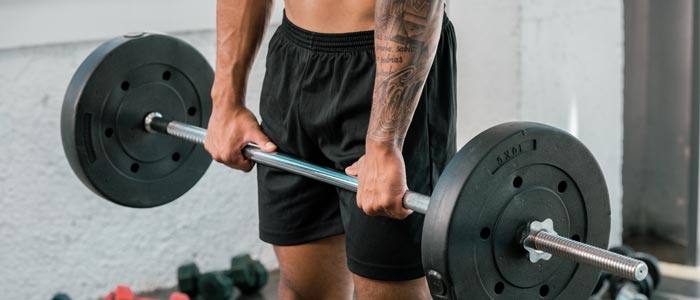 Man holding barbell for wrist rotations