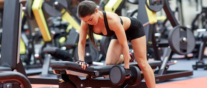 Woman using the pull section of the weight bench workout plan