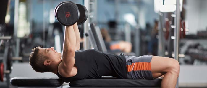 Man using the push section of the weight bench workout plan