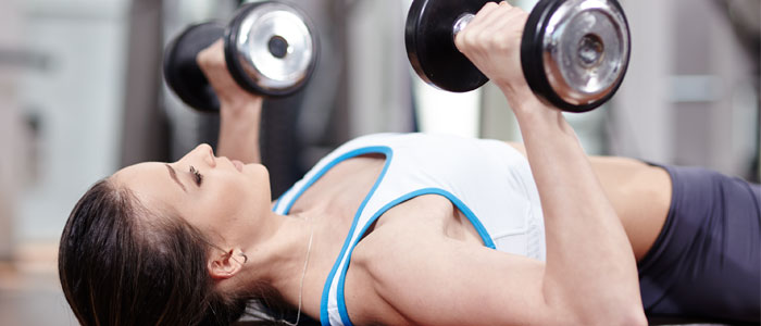 woman doing a dumbbell bench press