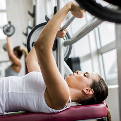 Woman bench pressing barbell