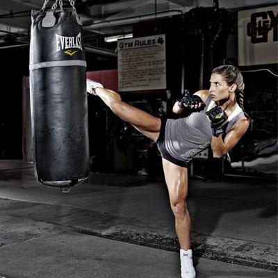 woman kicking a boxing punch bag