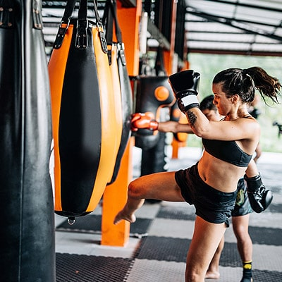women training in a gym with boxing punch bags