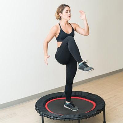 Woman doing aerobics on a fitness trampoline