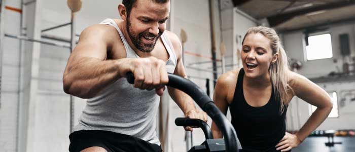 Man on an exercise machine with a woman coaching him