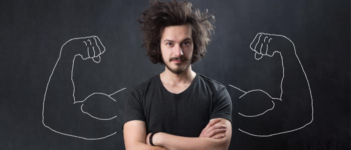 A man stood in front of a chalk board with muscle arms drawn behind him