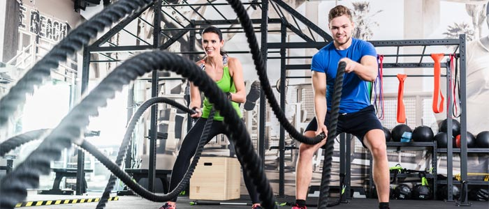 Two people training with battle ropes