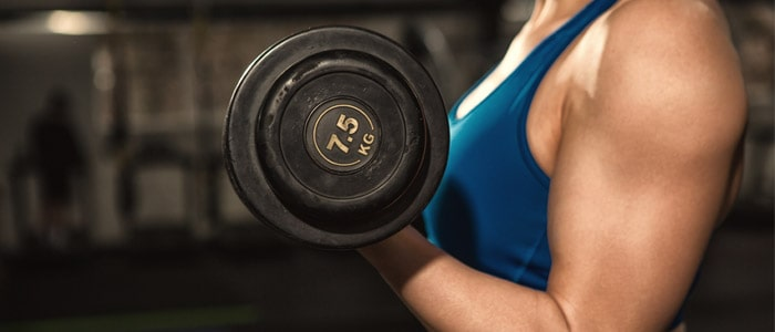 Close up shot of a woman bicep curling a dumbbell